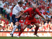 Photo: Henry Browne.<br /> Wales v England. FIFA World Cup Qualifying match.<br /> 03/09/2005.<br /> John Hartson of Wales holds off Jamie Carragher of England.