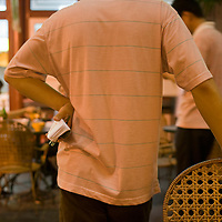 Asia, China, Beijing, Waiter stands with hands on hip at sidewalk Chinese restaurant at nighttime along Dong An Plaza