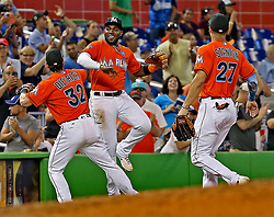 July 16, 2017 - Miami, FL, USA - The Marlins' Marcell Ozuna celebrates with teammates Derek Dietrich and Giancarlo Stanton  after he went high on the left field wall to rob the Dodgers' Kiki Hernandez of a homerun in the sixth inning as the Miami Marlins host the Los Angeles Dodgers on Sunday, July 16, 2017. (Credit Image: © Patrick Farrell/TNS via ZUMA Wire)