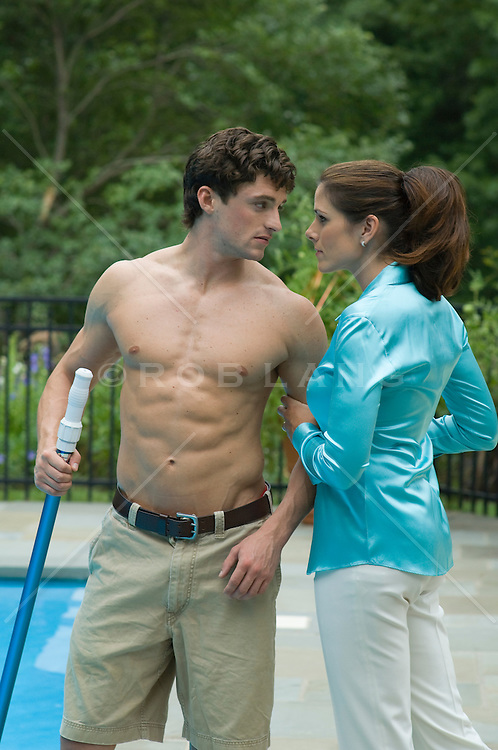Woman grasping her shirtless pool boy's arm, both looking at each other