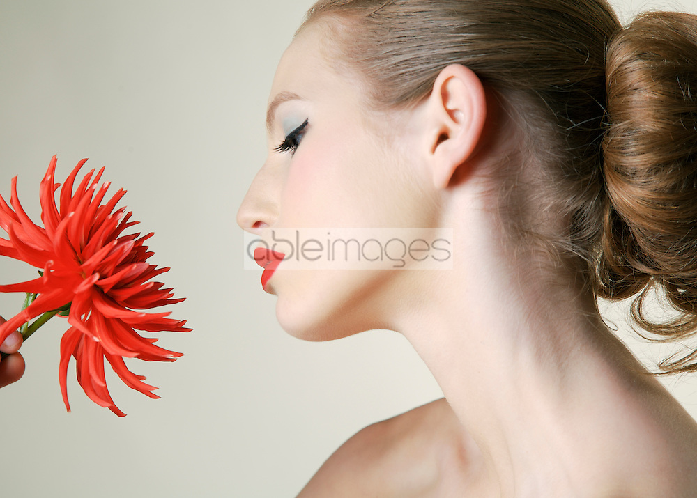 Close up of young beautiful woman holding red dahlia