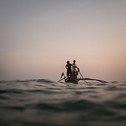 Fishermen leave in a bota at sunset.