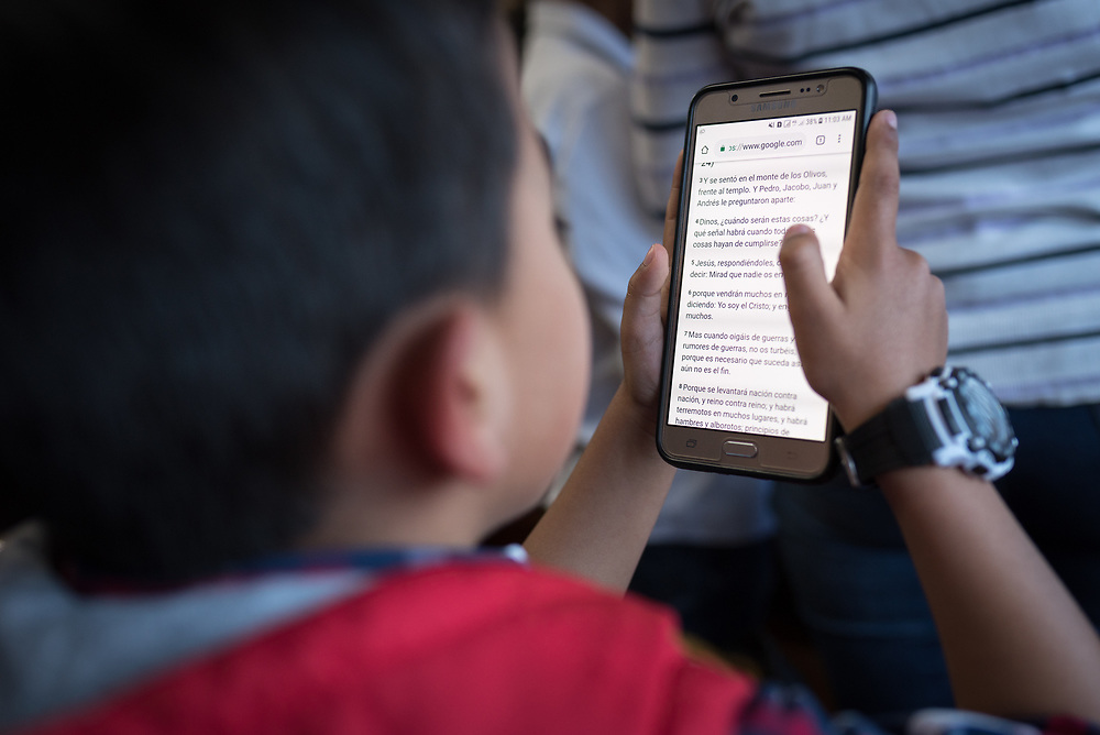 18 November 2018, Bogotá, Colombia: A young boy reads the Bible on the screen of a telephone during Sunday service at the Church of San Lucas. The church of San Lucas ('Saint Lucas') of the Evangelical Lutheran Church of Colombia, brings together a congregation of some 100 people in the southern areas of Bogotá. Located in the Kennedy area, the church has recently celebrated 50 years. As part of its ministry, the church runs a school and college, The Colegio Evangelico Luterano de Colombia (CELCO) San Lucas, offering education to just over 1,000 students aged 3-18. The school started as a social initiative offering care for children aged 0-4 in Bogotá's less wealthy neighbourhood, allowing the parents opportunities to go to work. 36 years after its foundation, the school employs 56 staff, of which 36 are teachers.