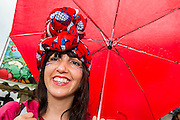 Members of a choir over 100 strong shelter from the rain inbetween performances. The 2013 Glastonbury Festival, Worthy Farm, Glastonbury. 27 June 2013. © Guy Bell, guy@gbphotos.com, all rights reserved