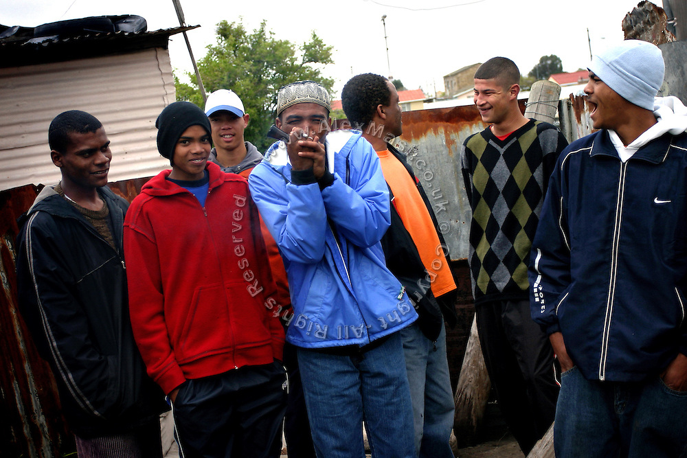 Youngsters smoking Mandrax (methaqualone) and Marijuana in their backgarden, in Cape Town, RSA. Initially marketed as a sedative or sleeping tablet by the French pharmaceutical giant Roussell Laboratories, it turned out to be highly addictive and banned in 1977. Sold illegally in South Africa, it is smoked in conjunction with Marijuana and it is the most widely used drug in the Western Cape, sold at about 30 Rands (about 3 UK pounds) per tablet. It is crushed and smoked in pipes or bottlenecks. It makes the user feel relaxed, clam and peaceful and everything looks perfect, while turning aggressive when the effect is wearing off. It requires increased usage in order to achieve the same effects and depression feelings are not uncommon with use. According to the Cape Town Drug Counselling Centre (CTDCC) it is a really difficult habit to break in impoverished communities where young unemployed are left on their own with no government help or other activities apart from crime and gansgterism. Social injustice, weakened family links and a feeling of 'not-belonging' are also causes of problems upon the 'coloured' communities in South Africa.