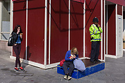 Eating women and a Met Police officer on a street corner in Leicester Square in central London. In a campaign to combat street crime, Met police have increased a noticeable presence by standing on a plinth slightly above the crowds of this busy tourist location in the West End. Next to the officer, is a woman tucking in to a lunchtime sandwich while a young woman enjoys an ice cream.