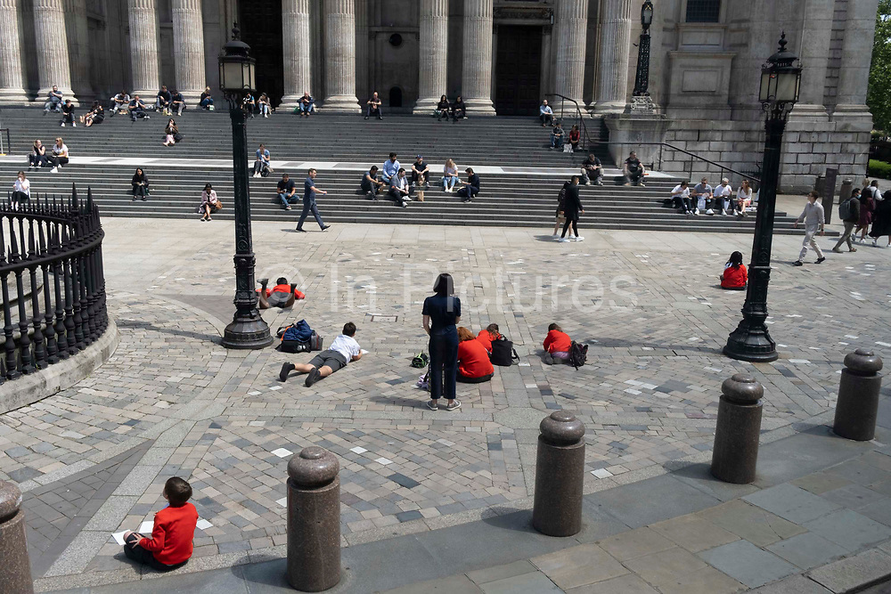 Wearing red school uniform jumpers, a group of school children enjoy warm sunshine during a day of outdoor learning in St Pauls Cathedral churchyard in the City of London, the capitals financial district, on 23rd June 2021, in London, England.
