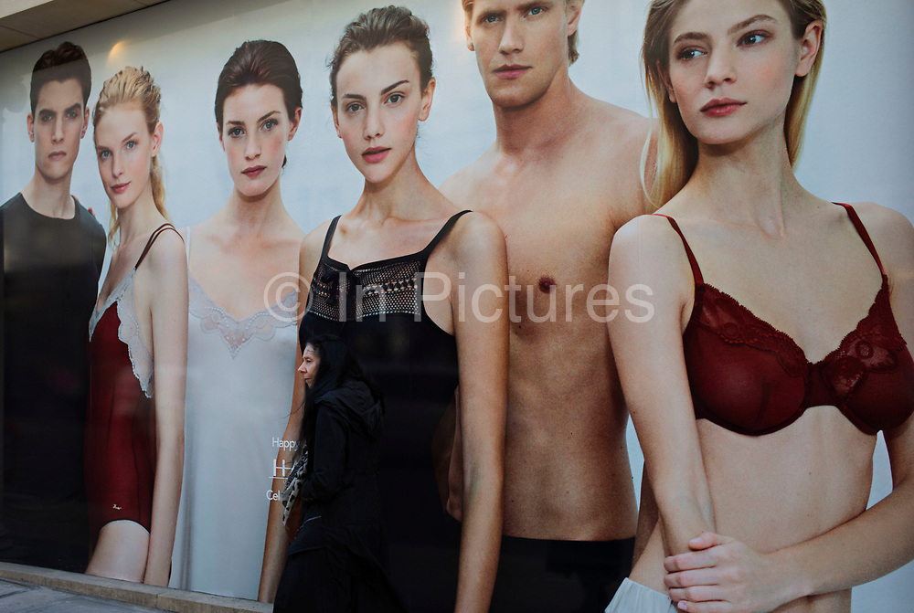 Hoarding outside a shop under refurbishment makes an interesting street scene on New Bond Street, London, UK. A weird visual juxtaposition is created as people integrate with the large scale printed photograph. Woman blends in to an underwear advertising picture.