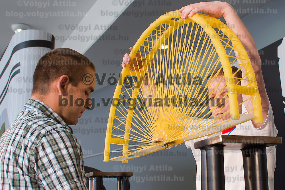 Competitors prepare their construction for the testing the Spaghetti Bridge World Championship in Budapest, Hungary on May 24, 2013. ATTILA VOLGYI