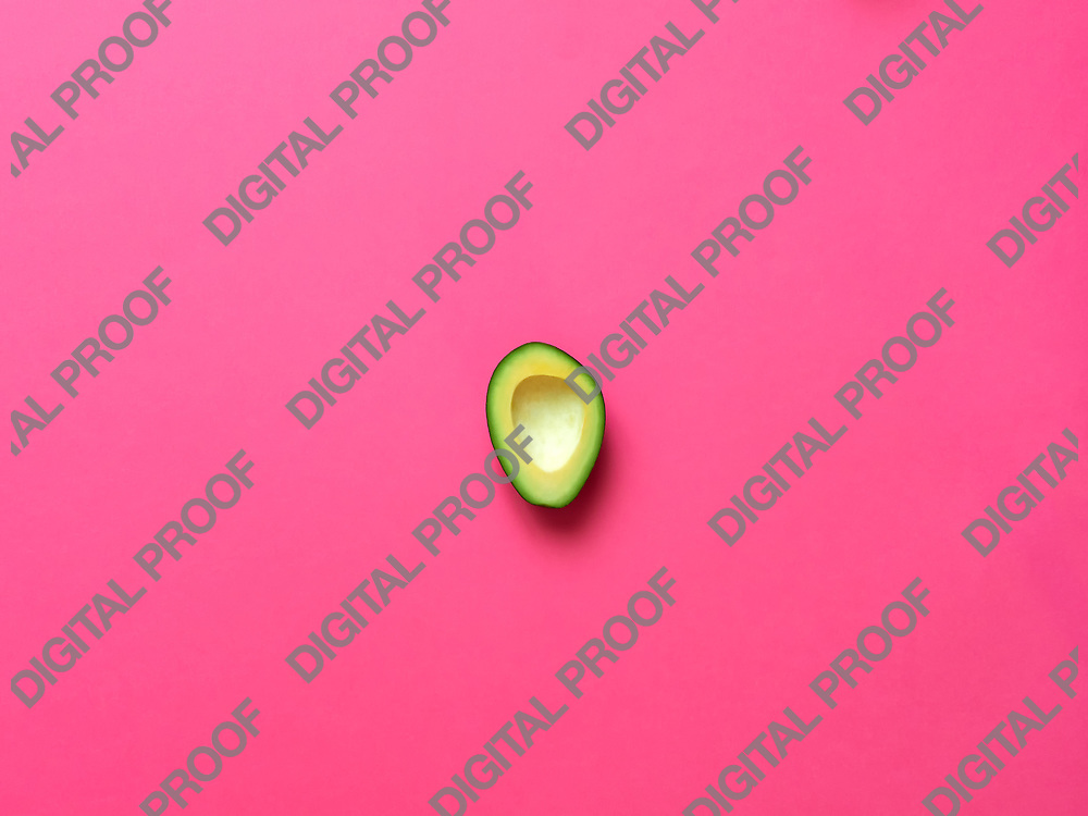 Avocado without seed isolated in fuscia background viewed from above - flatlay look
