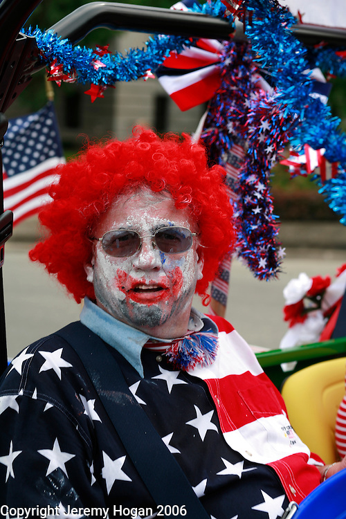 A clown, with smeared makeup, and wearing an American flag shirt, passes during the annual 4th of July parade in Bloomington, Indiana.