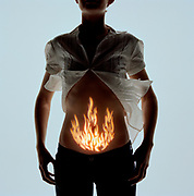 Woman with flame pattern projected onto stomach, mid section