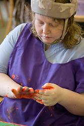 Day Service user with learning disability hand painting ,