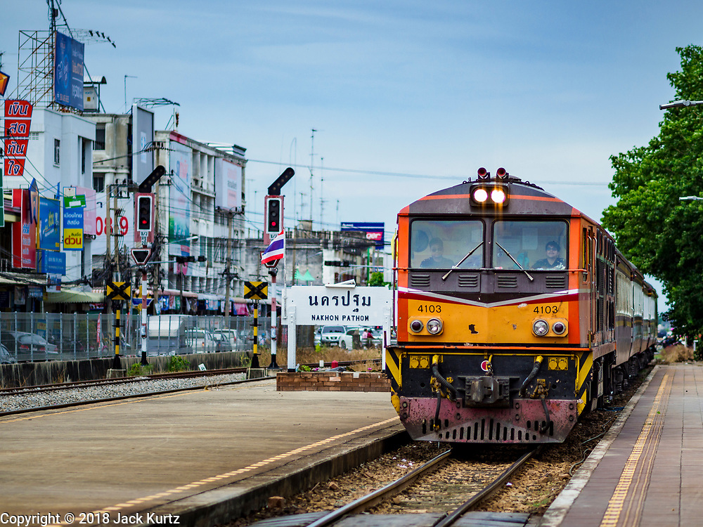 10 JULY 2018 - NAKHON PATHOM, THAILAND:  A southbound train comes into the station in Nakhon Pathom. Nakhon Pathom is about 35 miles west of Bangkok. It is one of the oldest cities in Thailand, archeological evidence suggests there was a settlement on the site of present Nakhon Pathom in the 6th century CE, centuries before the Siamese empires existed. The city is widely considered the first Buddhist community in Thailand and the nearly 400 foot tall Phra Pathom Chedi is considered the first Buddhist temple in Thailand.    PHOTO BY JACK KURTZ