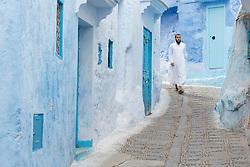 Man in white kaftan walking down blue alleys, Chefchaouen, Morocco