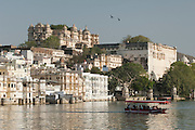 People crossing Lake Pichola on a boat near the City Palace in Udaiper, also known as the City of Lakes, Rajasthan, India