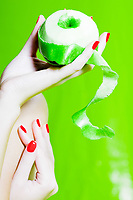 beautiful caucasian woman hands show a peeled apple studio on green background