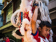 27 JANUARY 2017 - BANGKOK, THAILAND: A member of a Chinese lion dance troupe relaxes after a performance at a Chinese Shrine in Bangkok on Chinese New Year. 2017 is the Year of the Rooster in the Chinese zodiac. This year's Lunar New Year festivities in Bangkok were toned down because many people are still mourning the death Bhumibol Adulyadej, the Late King of Thailand, who died on Oct 13, 2016. Chinese New Year is widely celebrated in Thailand, because ethnic Chinese are about 15% of the Thai population.       PHOTO BY JACK KURTZ