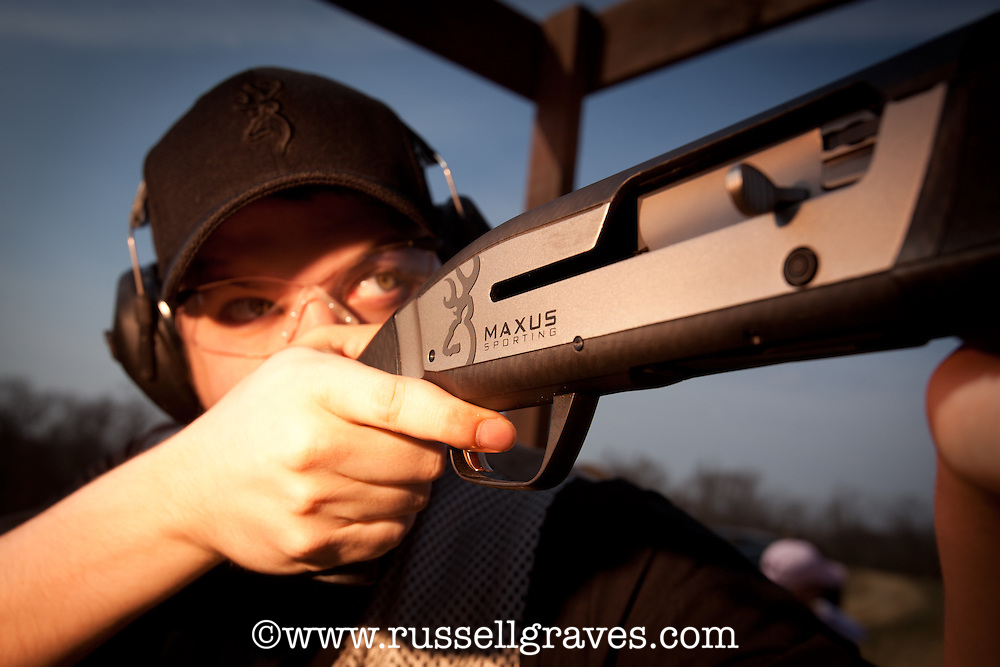 SHOOTER USING A BROWNING SHOTGUN TO SHOOTING AT CLAY PIGEONS FROM A SPORTING CLAYS COURSE