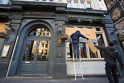 © Licensed to London News Pictures.01/12/2020. London, UK. Workers take off the planks covering the windows of a pub in Leicester Square, central London as second national lockdown will end tomorrow and pubs will be reopen. Photo credit: Marcin Nowak/LNP