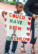 """Sevyn Coleman, 5, stands outside the Florida Capitol building in Tallahassee, July 20, 2013, holding a sign featuring an image of 17-year-old Trayvon Martin, who was fatally shot in early 2012. Coleman was with his mother, Dana Coleman, who was participating in a rally against racial profiling and Florida's """"stand-your-ground"""" self-defense law.  (Photo by Carmen K. Sisson)"""