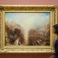 London, UK - 8 September 2014: a gallery assistant walks past 'The Visit to the Tomb' by J.M.W. Turner, during the press preview of The EY Exhibition: Late Turner – Painting Set Free exhibition at Tate Britain