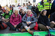 Climate change activists from the Extinction Rebellion group block the street at Bank in the heart of the City of London financial district in protest that the government is not doing enough to avoid catastrophic climate change and to demand the government take radical action to save the planet, on 25th April 2019 in London, England, United Kingdom. Extinction Rebellion is a climate change group started in 2018 and has gained a huge following of people committed to peaceful protests.