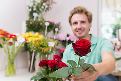 Portrait of mid adult man holding flowers, smiling