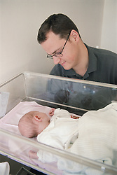 Father looking down at new born baby lying in cot on Maternity Unit in hospital,