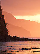 People swim at dusk at Ke'e Beach, Ha'ena State Park, Kaua'i, Hawai'i