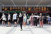 People, some wearing masks to prevent the spread of Covid-19 and some not, leaving the platforms of Leeds train station with the departures and announcements board overhead on 18th July, 2021 in Leeds, United Kingdom. Headlines have reported widespread confusion among users of public transport as to the circumstances where they should wear a face covering, with the UK government removing the legal requirement to do so, allowing different rail companies to make up their own rules.
