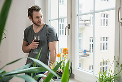 Mid adult man looking through window in living room and drinking red wine, Munich, Bavaria, Germany