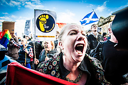 Activists demonstrate as UK Independence Party leader Nigel Farage talks to the press during European election campaigning on May 9, 2014 at The Corn Exchange, Edinburgh.
