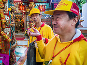 """23 JUNE 2015 - MAHACHAI, SAMUT SAKHON, THAILAND:  Men bang prayer gongs at the beginning of the procession for the City Pillar Shrine in Mahachai. The Chaopho Lak Mueang Procession (City Pillar Shrine Procession) is a religious festival that takes place in June in front of city hall in Mahachai. The """"Chaopho Lak Mueang"""" is  placed on a fishing boat and taken across the Tha Chin River from Talat Maha Chai to Tha Chalom in the area of Wat Suwannaram and then paraded through the community before returning to the temple in Mahachai.  PHOTO BY JACK KURTZ"""