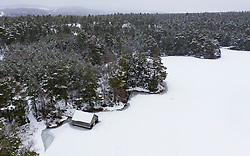 Aviemore, Scotland, UK. 4 February 2021. Loch Vaa is completely frozen and offers opportunity to walk across it. A small boathouse is now icebound and three ladies from the InVaa Dookers wild swimming group use axes to break the ice to allow them to soak in the icy water for a few minutes. Pic; Aerial view of  boathouse on frozen Loch Vaa.  Iain Masterton/Alamy Live News
