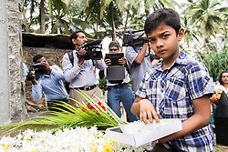 © Licensed to London News Pictures. 26/12/2014. Sri Lanka, UK 10th year commemorations of the Indian Ocean Tsunami, in Sri Lanka. Here in Peraliya, a young boy places makes an offering at the Tsunami memorial, in remembrance of the 1500 people that lost their lives on the fated Tsunami Train that derailed nearby,  and to the untold victims nationwide, estimated to be 40,000 people. Photo credit : Sam Spickett/LNP