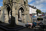 Ladies have tea in afternoon sunshine beneath the clocktower in Machynlleth, on 12th September 2018, in Machynlleth, Powys, Wales. To celebrate the 21st birthday of Viscount Castlereagh, the townspeople subscribed to the erection (at the town's main road intersection) of the clock tower, which has become widely known as the symbol of Machynlleth. The tower, which stands on the site of the old town hall, is the first thing many visitors will notice. The foundation stone was laid on 15 July 1874.