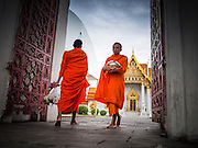 "21 JULY 2013 - BANGKOK, THAILAND:   Buddhist monks walk in and out of Wat Benchamabophit on the first day of Vassa, the three-month annual retreat observed by Theravada monks and nuns. On the first day of Vassa (or Buddhist Lent) many Buddhists visit their temples to ""make merit."" During Vassa, monks and nuns remain inside monasteries and temple grounds, devoting their time to intensive meditation and study. Laypeople support the monastic sangha by bringing food, candles and other offerings to temples. Laypeople also often observe Vassa by giving up something, such as smoking or eating meat. For this reason, westerners sometimes call Vassa the ""Buddhist Lent.""      PHOTO BY JACK KURTZ"