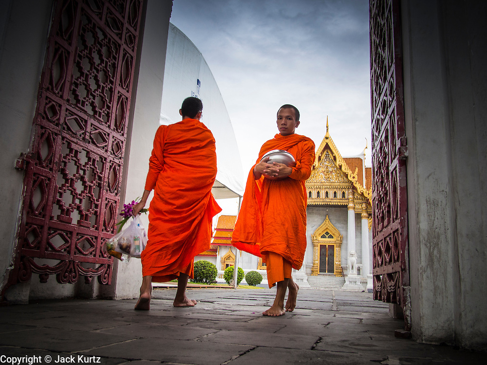 """21 JULY 2013 - BANGKOK, THAILAND:   Buddhist monks walk in and out of Wat Benchamabophit on the first day of Vassa, the three-month annual retreat observed by Theravada monks and nuns. On the first day of Vassa (or Buddhist Lent) many Buddhists visit their temples to """"make merit."""" During Vassa, monks and nuns remain inside monasteries and temple grounds, devoting their time to intensive meditation and study. Laypeople support the monastic sangha by bringing food, candles and other offerings to temples. Laypeople also often observe Vassa by giving up something, such as smoking or eating meat. For this reason, westerners sometimes call Vassa the """"Buddhist Lent.""""      PHOTO BY JACK KURTZ"""
