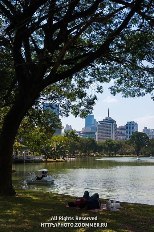 People relax on grass near lake in Lumpini park, Bangkok, Thailand