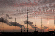 The sky after sunset silhouetting boat masts at the Ala Wai Boat Harbor in Waikiki.