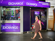 08 JULY 2015 - BANGKOK, THAILAND:  A woman walks past an exchange booth in Bangkok Wednesday. Thai financial markets and the Thai Baht both lost value Wednesday. The stock market, the Stock Exchange of  Thailand (SET) closed at 1,470.25, down 13.52 or 0.91%, from Tuesday. The Thai Baht closed at 33.90 Baht to 1 US Dollar, it's lowest point since September 2009. Economists blamed the drop in the Chinese stock markets and uncertainty over the EU's handling of the Greek budget crisis for the drops in Thai markets.   PHOTO BY JACK KURTZ