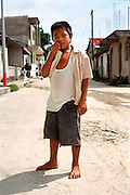 Portrait barefoot indigenous Mayan child standing in middle of main road.