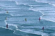 An aerial view looking down from a highpoint, on to the shallows and surf of waters near Lynton, Devon, England. Windsurfers traverse the windy seascape on a spring day on this south-western coast, one of England's warmest regions. Here, young surfers and ocean adventurers travel to these parts where the beaches are level and where the waves arrive at the coast in perfectly-formed breakers. In the picture, one surfer has fallen from their board, the sail now horizontal in the water. But the others are upright and travelling across the wind, expertly riding the waves.