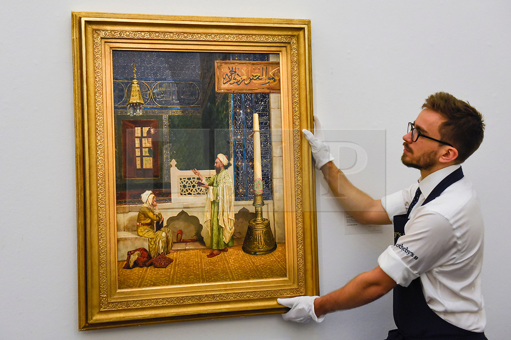 """© Licensed to London News Pictures. 11/10/2019. LONDON, UK. A technician presents """"Koranic Instruction"""", 1890, by Osman Hamdy Bey, (Est GBP3-6m).  Preview of works from the Najd Collection of orientalist paintings at Sotheby's in New Bond Street, which record daily life in the historic Arab, Ottoman and Islamic worlds  All 155 paintings are on public view 11- 15 October, with 40 works to be auctioned on 22 October.  Photo credit: Stephen Chung/LNP"""