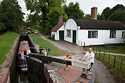 Father and son close a canal lock on the Grand Union canal at Lowsonford in Warwickshire. The is lock is right beside a still functioning lock keepers cottage.