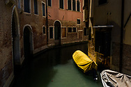 A boat covered in yellow and tied to the edge of a narrow canal in Venice, Italy