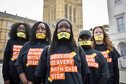 "© Licensed to London News Pictures. 14/10/2107. London, UK. Girls prepare to take part in the ""The Walk For Freedom"", marching around the capital demonstrating against modern slavery.  The protest is co-ordinated with other walks which abolitionist group A21 is staging in 400 cities around the world on the same day. The facemasks represents the silence of modern slaves. Photo credit : Stephen Chung/LNP"
