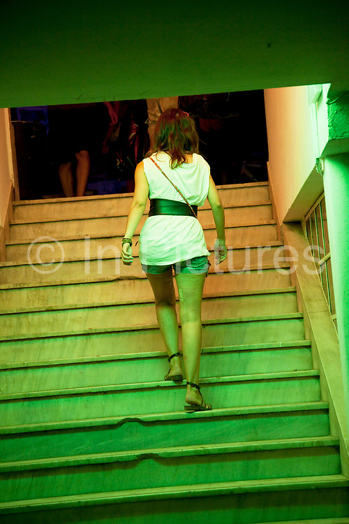 Woman walking up the steps at Six Dogs a trendy outdoor bar in the Monastiraki area. six d.o.g.s is a day & night cultural entertainment center at the heart of Athens (Monastiraki), which organically combines each one of its elements: a Project Space (non-profit space for presenting visual art projects and other likewise one-off events), a Bar, a Café, a Gig Space for hosting live gigs, theatrical performances, bazaars, workshops, talks, screenings, and educational programs, and a vivid 600m2 Back-Garden. six d.o.g.s is not introduced as a new space, but rather, as a new model for a space. It is suggested as a space which aims at creating a high-profile dynamic nucleus of cross-genre activities right in the heart of the Historic Center, initialized by an equally dynamic experienced group of young art professionals, aiming at being both avant-garde and pop, sharing similar qualities.  Athens is the capital and largest city of Greece. It dominates the Attica periphery and is one of the world's oldest cities, as its recorded history spans around 3,400 years. Classical Athens was a powerful city-state. A centre for the arts, learning and philosophy.