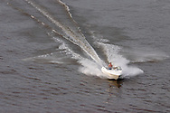 Highland, N.Y. - A man drives a motor boat down the Hudson River near the Mid-Hudson Bridge, which links Highland and Poughkeepsie, on July 8, 2006. ©Tom Bushey